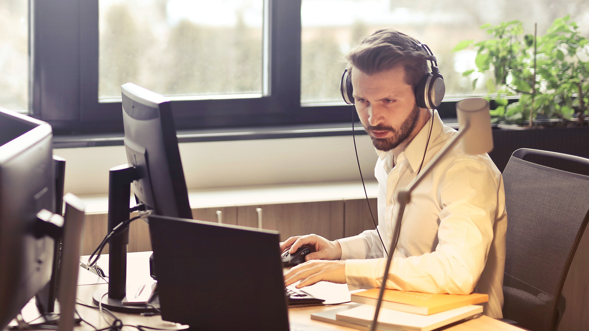 Business man using a computer with headphones