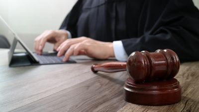 Magistrate using tablet near gavel